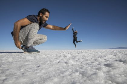 Couple playing with perspective in desert salt flats
